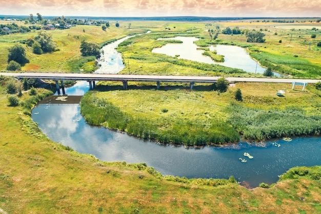 Летний сельский пейзаж. с высоты птичьего полета. вид на деревню, реку, зеленые поля и дорогу