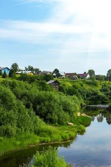 강 근처에 목조 주택이 있는 러시아 북부 마을의 여름 시골 풍경