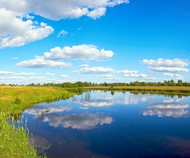 Летний бурный вид на озеро с отражениями облаков.