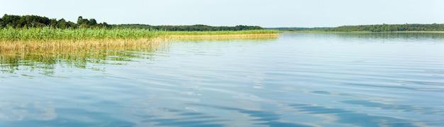 反対側の岸に小さな木立がある夏の急いでいる湖の景色。 3ショットステッチ画像。