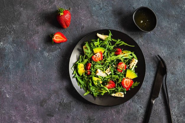 Summer salad bowl with arugula, strawberry, brie cheese, caraway and honey searved on black wall with black fork and knife. healthy eating concept. flatlay with copyspace. close up. hard light