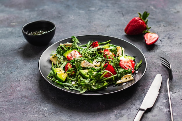 Summer salad bowl with arugula, strawberry, brie cheese, caraway and honey searved on black wall with black fork and knife. healthy eating concept. top view with copyspace. close up. hard light