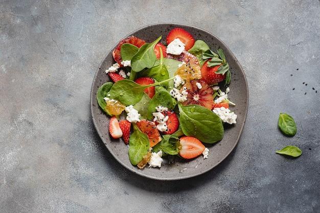 ほうれん草、イチゴ、カッテージチーズ、ブラッドオレンジ、蜂蜜のサマーサラダボウル。