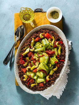 붉은 쌀, 신선한 호박, 고추와 파란색 배경에 캐슈와 자몽의 여름 샐러드