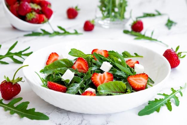 ストロベリーサラダレシピの周りのイチゴの果実とルッコラフェタチーズとイチゴの夏のサラダ