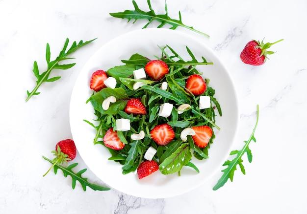 ルッコラほうれん草とイチゴの夏のサラダは、フェタチーズとカシューナッツを残します