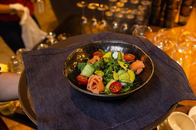 ウェイターを手にした白いお皿に夏のサラダ。 Premium写真