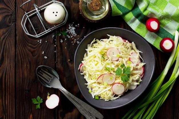 나무 테이블에 올리브 오일을 얹은 신선한 양배추와 무를 곁들인 여름 샐러드