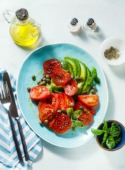 Summer salad with ripe tomatoes and avocado with capers in a blue plate on the table