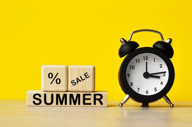Summer sale .alarm 시계와 노란색 배경에 텍스트가 있는 나무 큐브. 관리 및 비즈니스에 대한 개념입니다.