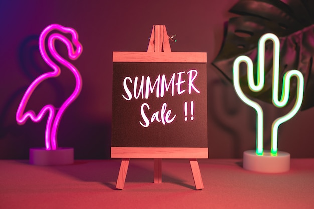 Летняя распродажа на доске с фламинго и кактус неоновый розовый и синий свет на столе