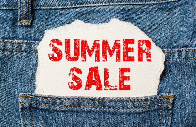 Летняя распродажа на белой бумаге в кармане джинсов синих джинсов