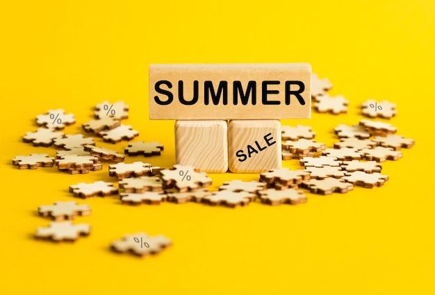 여름 세일 . 노란색 배경에 텍스트가 있는 퍼즐과 나무 큐브. 관리 및 비즈니스에 대한 개념입니다.