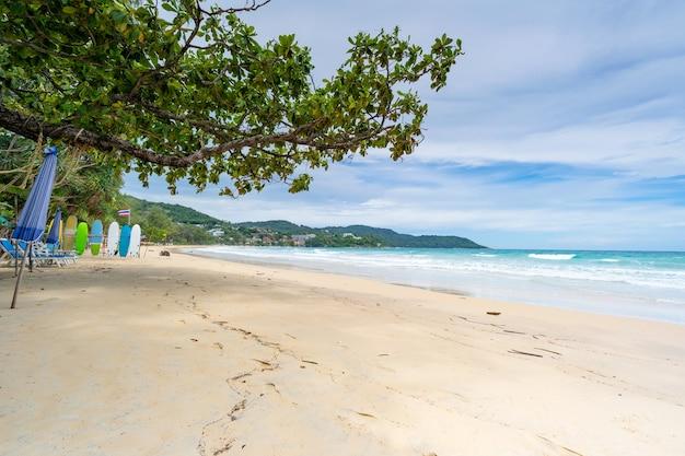 해변 의자와 파도 해포가 모래사장에서 충돌하는 여름 모래 해변 청록색 바다 물과 바다 위의 푸른 하늘 흰 구름 여름 휴가를 위한 자연 배경 여행 웹사이트
