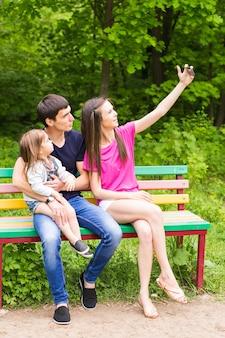 公園で彼女のスマートフォンでselfiesを取って幸せな若い家族の夏のシーン。