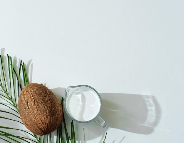 ガラスの水差しにヤシの葉、ココナッツ、ビーガンの有機ココナッツミルクを入れた夏のシーン。健康的な食事の概念。コピースペースのある最小限のフラットレイ。
