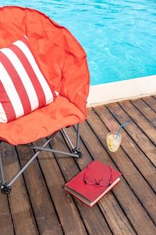 Summer scene with swimming pool, chair, drink and book. concept of vacation or leisure time in summer