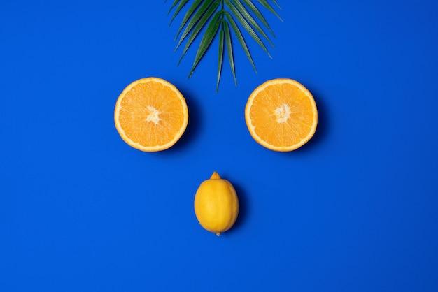Летняя сцена с тропических пальмовых листьев, апельсина и лимона на синем фоне. минимальная эстетика. плоский стиль. копировать пространство