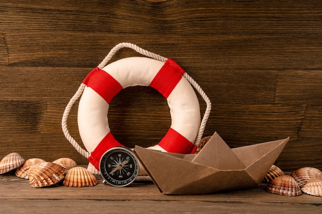 夏の海のバナー。救命浮輪、貝殻、木製の背景に紙のボート
