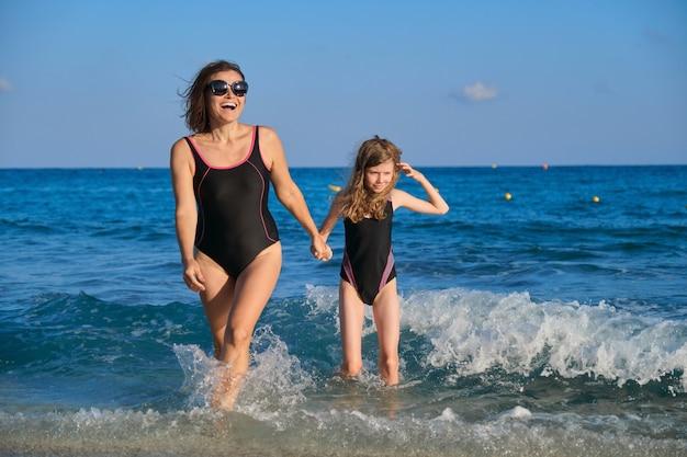 Летний морской семейный отдых, счастливая мать и дочь в купальниках, гуляющие по берегу моря, держась за руки, наслаждаясь водой и вечерним закатом солнца