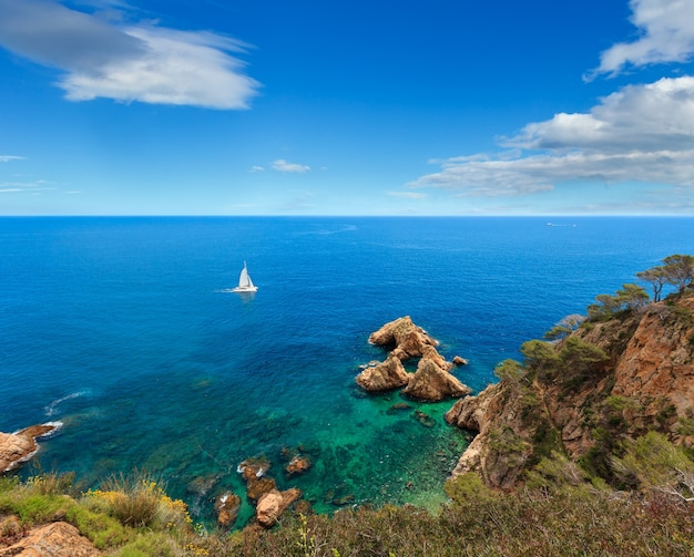 Пейзаж скалистого побережья моря лета с катамараном, коста брава, испания. вид сверху.