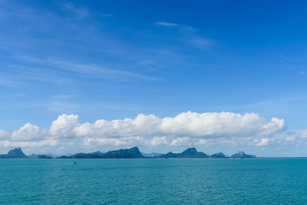 Summer seascape with green island and blue sky background