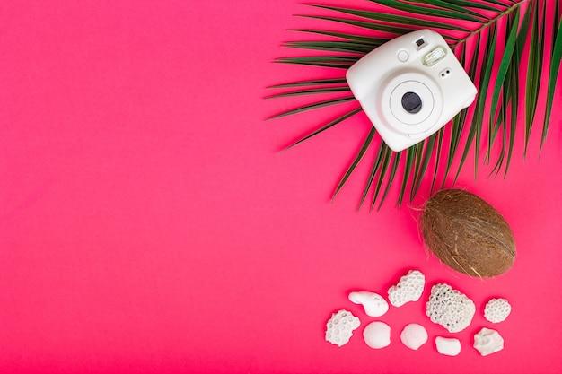 Летний набор фотоаппарата, очков, шляп и кораллов на розовом фоне