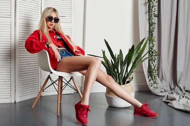 빨간 가죽 재킷을 입은 여름 섹시한 금발과 의자에 앉아 앞에 안경을 쓴 파란 데님 반바지. 완벽한 몸매와 아름다운 여성의 머리카락, 긴 다리와 머리카락. 러시아, 스베르들로프스크, 2018년 6월 13일