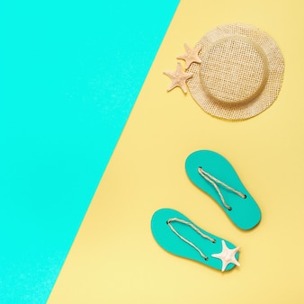 Summer shoes flip-flops, straw hat and small starfishes on bright paper surface