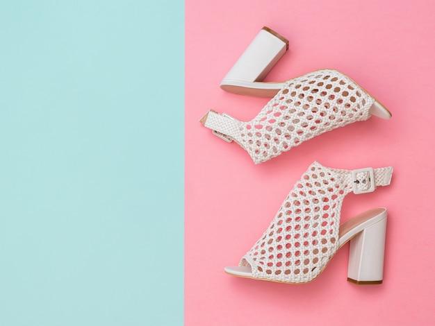 ピンクとブルーの背景に白い革で作られた夏の靴。女性のための夏の靴。フラットレイ。上からの眺め。