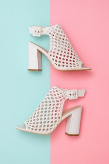 Summer shoes made of white leather on blue and pink
