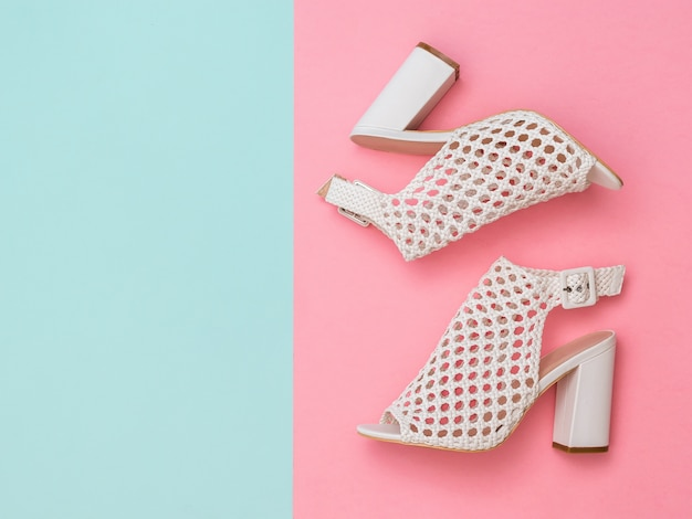 Summer shoes made of white leather on pink and blue background. summer shoes for women. flat lay. the view from the top.