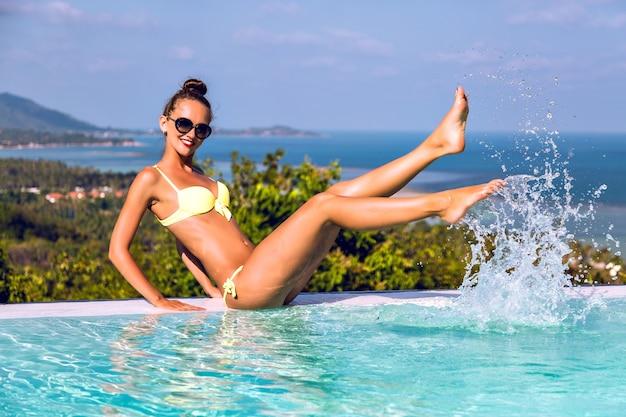 Riprese estive di felice giovane donna allegra che si diverte e che fa schizzi d'acqua con le sue mani alla piscina a sfioro della villa, vita di lusso, viaggi in un'isola esotica.