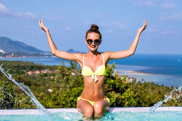Summer shoot of happy exited cheerful young woman having fun and making water splash by her hands at villa infinity pool, luxury living, travel at exotic island.