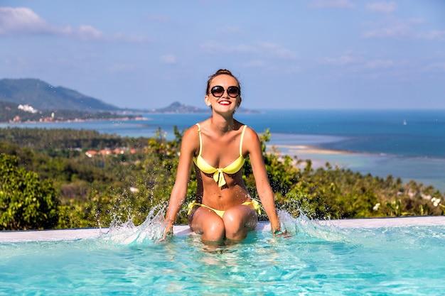 幸せな終了陽気な若い女性の楽しい夏の撮影は、ヴィラインフィニティプール、豪華な生活で彼女の手で水のしぶきを作って、エキゾチックな島に旅行します。