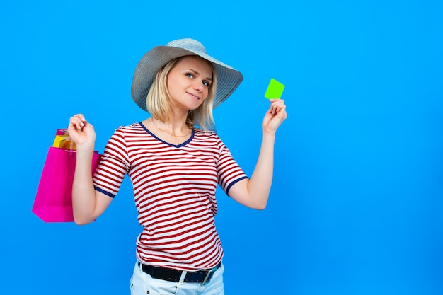 Summer shopping and sales. blonde caucasian woman in summer hat holding purple shopping bags and showing green credit card