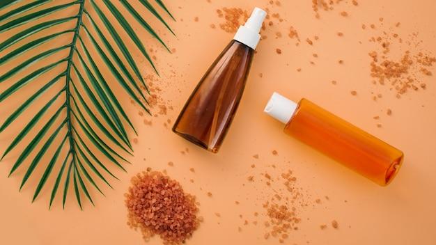 緑のヤシの葉の背景を持つ夏のスキンケア自然化粧品。フェイシャルトニックとクリーム、海塩。ホームスパ。