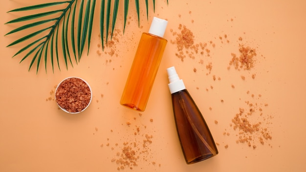 Summer skincare natural cosmetic products with green palm leaf background. facial tonic and cream, sea salt. home spa.
