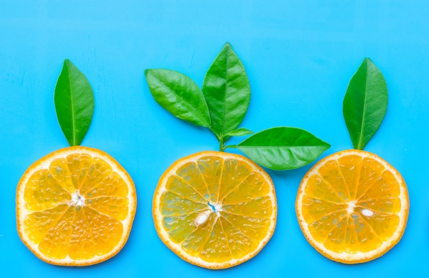 Summer of slice orange fruit with green leaves on blue background.