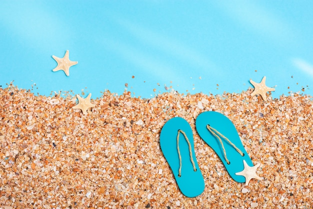 Summer slippers on beach with sand under sunlight, summer background with copy space. pastel colored. vacation by sea.