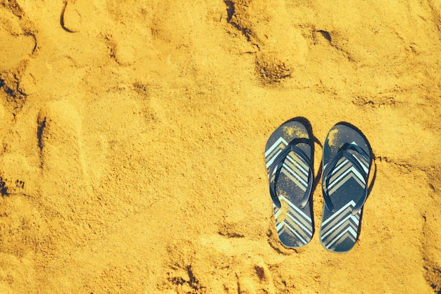 Summer slippers. navy blue flip flop on yellow sand beach background. holiday, vacation and travel concept