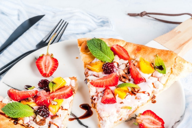 Summer snacks. food for party. fruit pizza with cream, currants, yogurt, strawberries, mango, peaches, bananas, blackberries, chocolate, walnuts, mint. on light blue table. copyspace