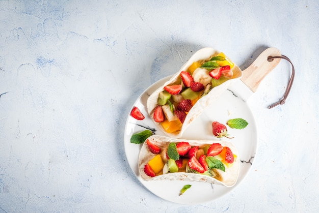 Summer snacks. food for a party. fruit tacos with strawberries, mangoes, bananas, chocolate, mint. on a light blue concrete table. copyspace top view