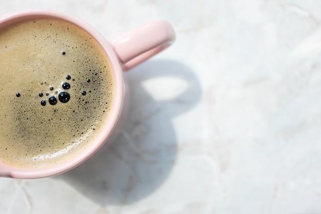 Летний безалкогольный напиток с пеной пузырей в розовой чашке на фоне мраморного стола с копией пространства, вид сверху. минималистская концепция образа жизни