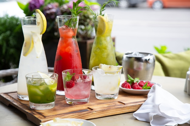 Summer soft drinks, a set of lemonades. lemonades in jugs on the table, the ingredients of which they are made are arranged around.
