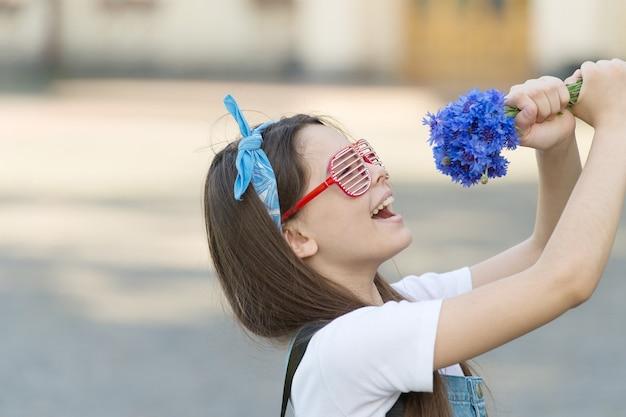 夏の歌。幸せな女の子はマイクとして花を保持します。花屋。フラワーアレンジメント。花屋。休日を祝う。花屋。エレガントな花を買う。イベント用のブーケやギフト。