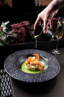 Летний суп окрошка с тигровой креветкой и свежим огурцом в черной тарелке