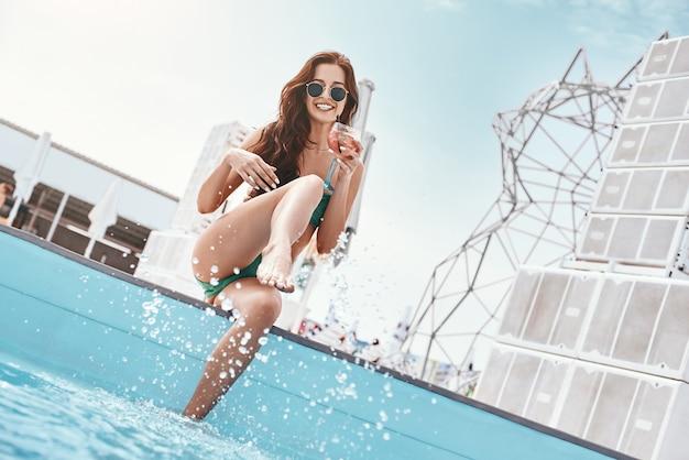プールの近くで楽しんでいる緑の水着でスリムなファッションモデルの夏のスプラッシュの肖像画