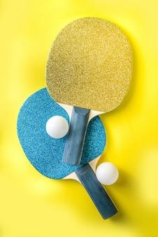 여름 스포츠 활동 개념. 유행 노란색 배경에 공 밝은 탁구 테니스 패들 라켓
