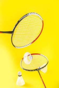 Концепция летних видов спорта две ракетки для бадминтона с воланами